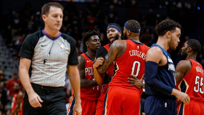 New Orleans Pelicans forward Anthony Davis (23) is held back by center DeMarcus Cousins (0) and guard Jrue Holiday (11) as he yells towards referee Brent Barnaky (36) after being ejected following his second technical foul during the second quarter at the Smoothie King Center.