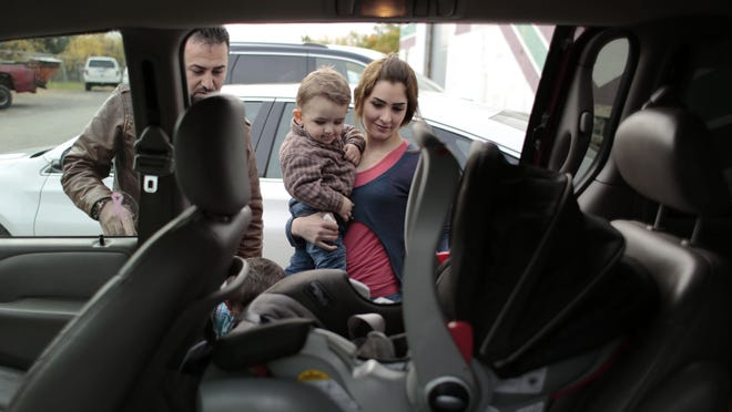Waseem Ilotte, left, and his wife, Lara Al Aso, load their son Aras Ilotte, 18 months old, all from Warren, into their vehicle after receiving aid at the Chaldean American Ladies of Charity Center on Friday, Oct. 10, 2014 in Troy.