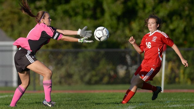 Greece Odyssey goalie Kristen Gielenfeldt, left, reaches for the ball as Palmyra-Macedon's Jamie Walker closes in during a regular season game at Greece Odyssey High School on Tuesday. Pal-Mac beat Odyssey 2-0.