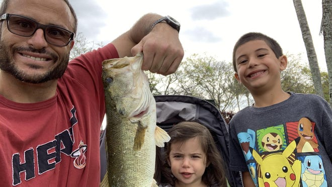 Using a Storm WildEye Swim Shad lure, Max Rudnet (right) caught this impressive bass while fishing with his father Michael Rudnet (left) and sister Mila (center).