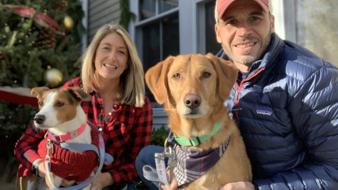 Amy and Danny Naples smile with their rescue dogs Divi and Buoy.