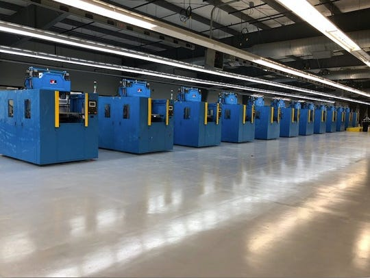 A line of molding machines awaits use at JDS Technologies'