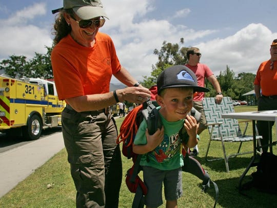 In this 2016 file photo, Upper Ojai Search and Rescue Team volunteer Mary Looby helps Alex Washburn try on a rescue climber pack during a safety fair. Looby played a crucial role in the recovery this week of a missing Ojai Valley at-risk teenager.