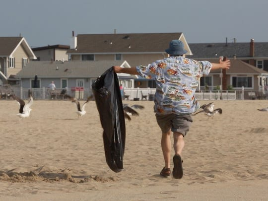 Jerry Carino chases seagulls as he cleans the beach at Jenkinsons. Asbury Park Press reporter Jerry Carino learns the duties of a Beach boy at Jenkinson's in Point Pleasant Beach, helping clean, walkway, showers, pick up the trash and get the beach pristine in the early morning hours before daily visitors put down their towels. Photo taken on July 6, 2015 in Point Pleasant Beach.