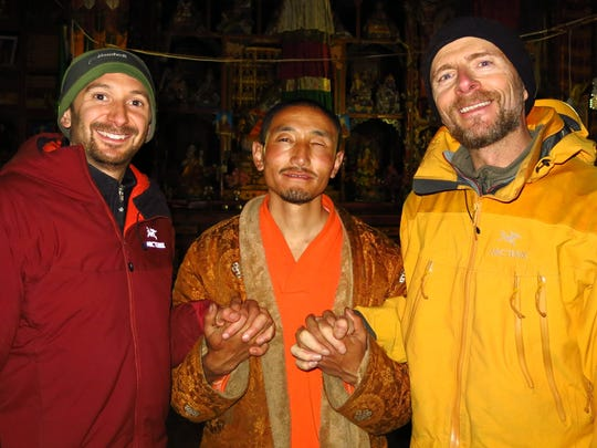Chris Strouthopoulos, left, and Mike Sullivan, right, celebrate their 2014 solar installation with Wonchu, a Tibetan Buddhist monk.
