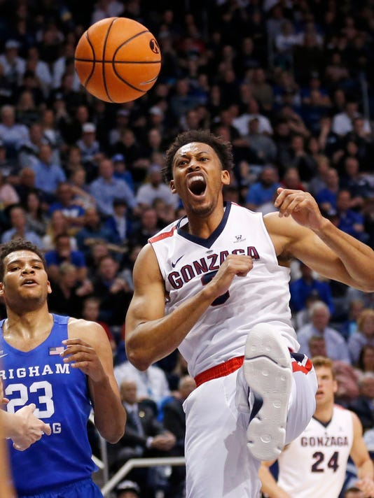 Gonzaga forward Johnathan Williams, right, reacts after dunking while BYU forward Yoeli Childs (23) watches during the first half of an NCAA college basketball game Saturday, Feb. 24, 2018, in Provo, Utah. (AP Photo/Rick Bowmer)