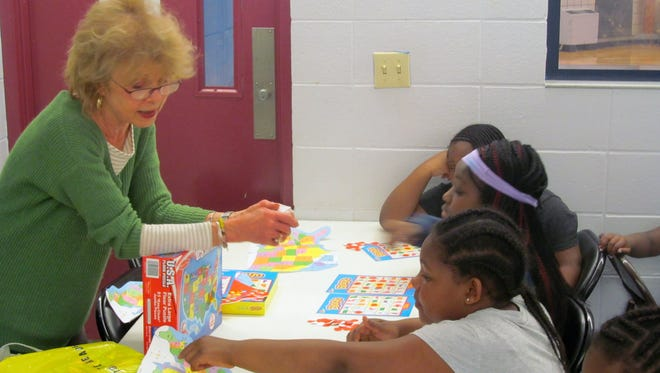 Carmen Swoffer-Penna, the outreach coordinator at the Anglican Church of the Good Shepherd, plays a geography Bingo game with children at Saratoga Apartments. The church does several outreach projects with the children there including gardening, cooking and holiday events such as a Christmas and Easter party.