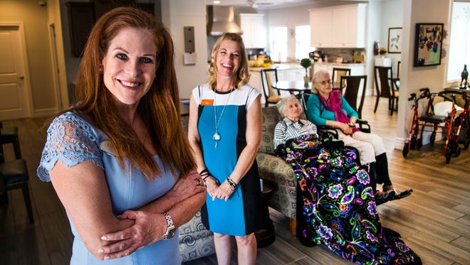PK Fields, CEO and founder of ElderSense (left) and Kristie Chadwick (second from left) care manager for Paradise Living Centers, pose in the living room at the Paradise Living Center assisted-living facility in Phoenix on May 22, 2017.