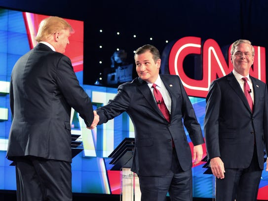 Ted Cruz reaches over to shake Donald Trump's hand