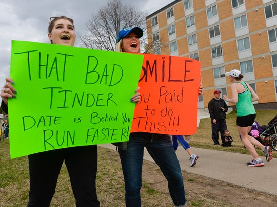 Amy Klein, left, Melrose, and close friend Lindsey Rieland, Sauk Centre, hold signs and cheer for the runners in Saturday's Earth Day Half Marathon. They had a family member and three friends running the race.