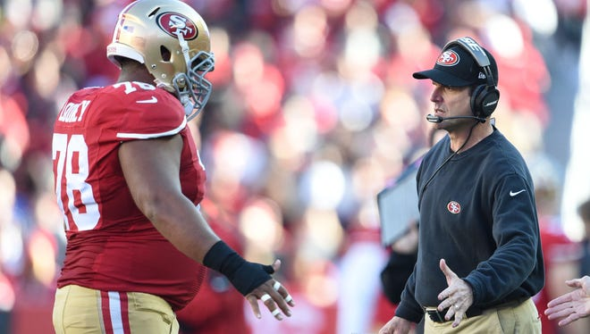 San Francisco 49ers head coach Jim Harbaugh (right) high-fives guard Joe Looney (78) against the Arizona Cardinals during the second quarter at Levi's Stadium.