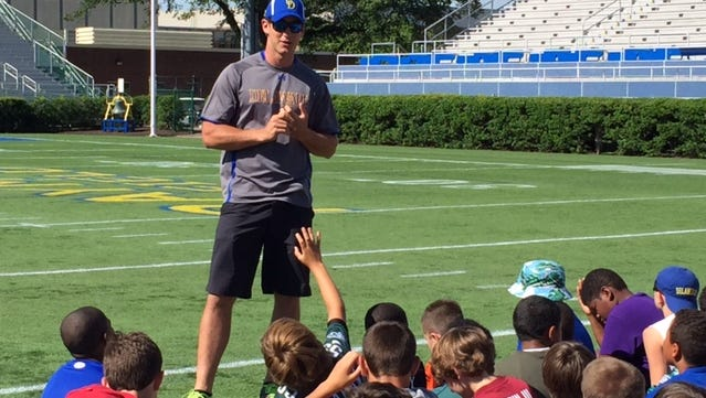 Former Delaware quarterback Pat Devlin talks to youth football campers at Delaware Stadium on Wednesday.