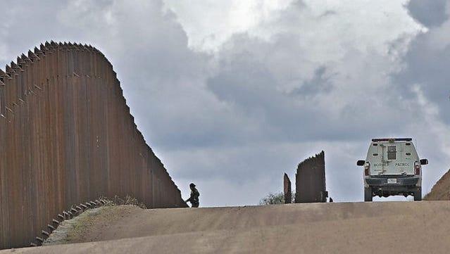 FILE - A Customs and Border Patrol agent patrols along the international border in Nogales, Ariz.