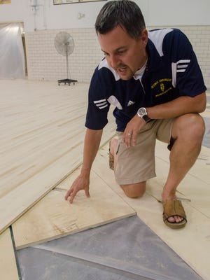 """Port Huron Northern Athletic Director Jason Kasparian shows the base and the top layer of the new floor Friday, July 6 of the Port Huron Northern gym. The floor is being replaced through the """"Fund Our Floor"""" campaign."""