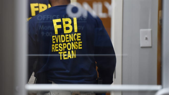 Investigators with the FBI gather evidence at the Opus Rx pharmacy at the Jackson Medical Mall on Thursday. The bureau, in cooperation with other federal and state agencies, executed search warrants at several pharmacies across the state on Thursday as part of an ongoing investigation.