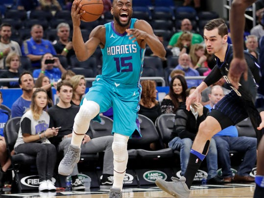 Charlotte Hornets' Kemba Walker (15) looks for a shot as he gets around Orlando Magic's Mario Hezonja (8) during the first half of an NBA basketball game Friday, April 6, 2018, in Orlando, Fla. (AP Photo/John Raoux)