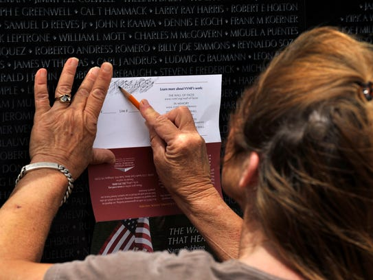 Val Loftin of Cisco makes a rubbing of a name on The Wall That Heals Thursday in Eastland. The three-quarter scale replica of the Vietnam Veterans Memorial will be on display at 930 E. Main St. until noon Sunday.