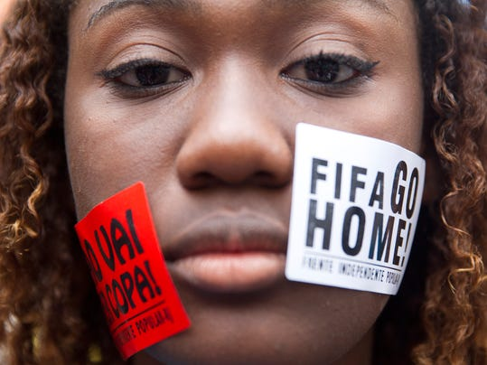 "A woman protests with signs pasted on her face that read ""FIFA Go Home"" and ""Will not have a Cup"" during a march against the World Cup 2014 at the Copacabana beach, in Rio de Janeiro, Brazil, Thursday, June 12, 2014. Protesters are demanding better public services and protesting the money spent on the soccer tournament. (AP Photo/Leonardo Wen)"