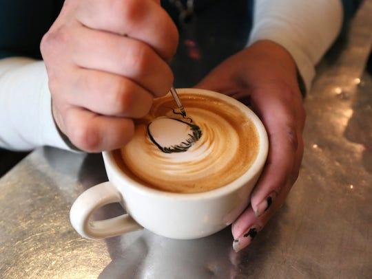 Barista Meagan Chauvot draws a face in a cappuccino