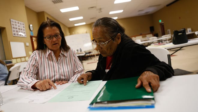 Julie Redhouse, left, translates for Rosie A. Chavez while looking over legal documents Wednesday at the Upper Fruitland Chapter House.