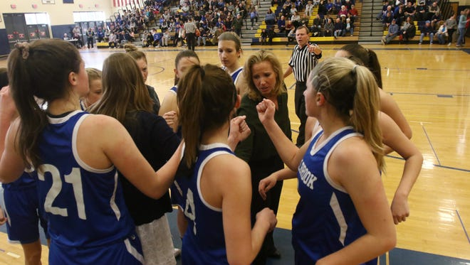 The Millbrook girls basketball team huddles during a timeout with its coaches.