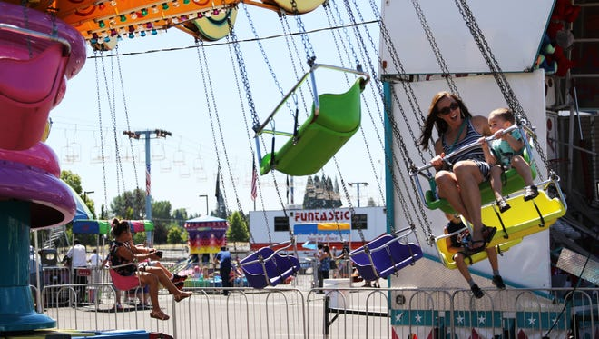 Bre and Mason Stover, of Salem, enjoy a ride on the swings at the Marion County Fair at the Oregon State Fairgrounds and Exposition Center, 2330 17th St. Salem, on Saturday, July 14. The fair continues through Sunday, July 15.