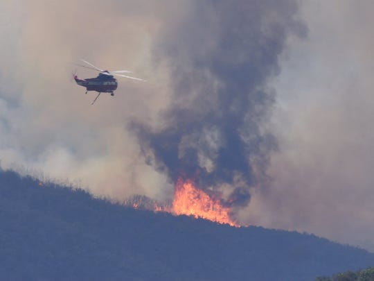 A helicopter drops water earlier this week on the eastern edge of a wildfire burning in Santa Barbara County.