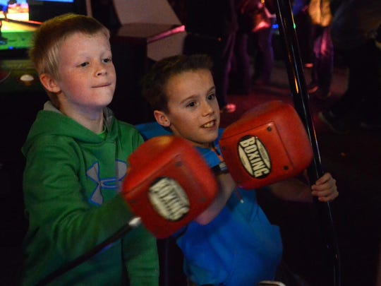 Ryan Kelly, 9, and Connor Ryan, 8, play a boxing video game.