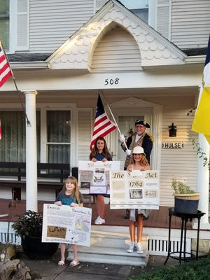 Bobbie Hulse holds the American flag with the winners of the Sons of the Plains Chap-ter SAR Poster Contest.