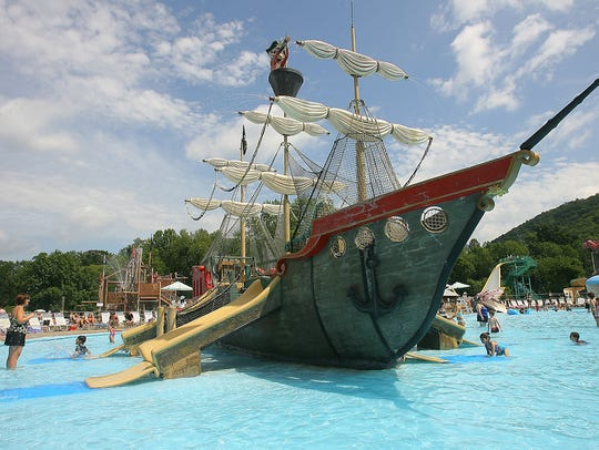 A large pirate ship with slides sits in the pool at