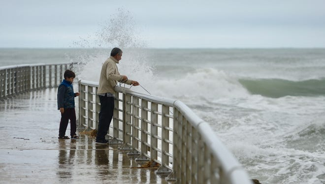 Santiago Jaramillo, 8, casts a net for bait with his grandfather, Julio Perez, on Wednesday, Jan. 3, 2018, on the pier on the Indian River County side of Sebastian Inlet State Park as waves from high winds batter the shore. As a cold-weather system moves over Central Florida, the National Weather Service in Melbourne issued an array of weather watches and warnings throughout the remainder of the week to brace Floridians for the unusual cold and wind pattern.