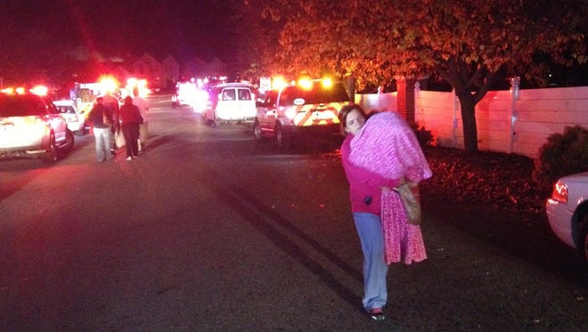 Celeste Brown, 32, carries her daughter Reese, 4, out of the Richmond Hill subdivision on the night of the explosion on Nov.12, 2012. They were visiting her parents' home.