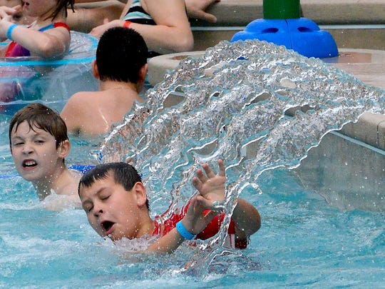 A boy tries to shield himself from water spraying into the lazy river in the new Atrium Waterpark at Zender's Splash Village hotel and waterpark in Frakenmuth.