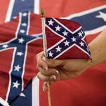 An employee holds up a Confederate flag during the manufacturing process at Alabama Flag and Banner on April 12, 2016 in Huntsville, Ala.