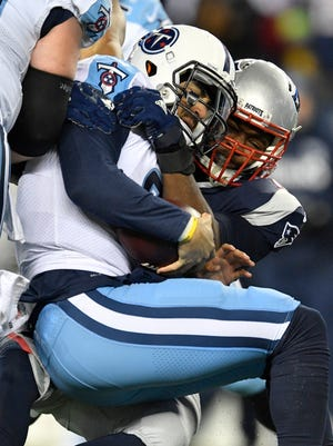 Titans quarterback Marcus Mariota (8) is sacked by Patriots defensive tackle Adam Butler (70) during the second half of the AFC divisional playoff game Saturday night.