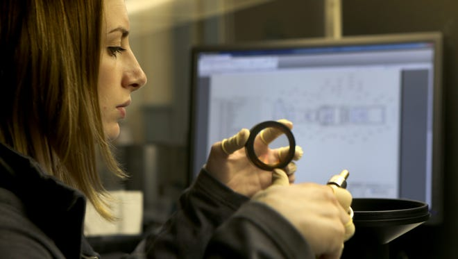 Emily Hoh, optics assembler at Navitar, builds a large lens that will be used in a planetarium projector.