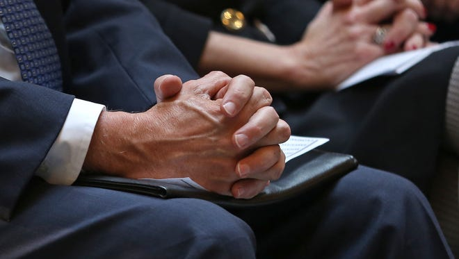 Governor Mike Pence holds his hands together in prayer during the 12th Annual Statehouse Prayer Service on the first day of the 2016 session, Tuesday, January 5, 2016.