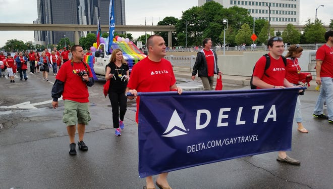 Marchers from Delta Airlines carry a banner as they walk ahead of the company's truck in the 43rd Annual Motor City Festival and Parade in Detroit on June 8.