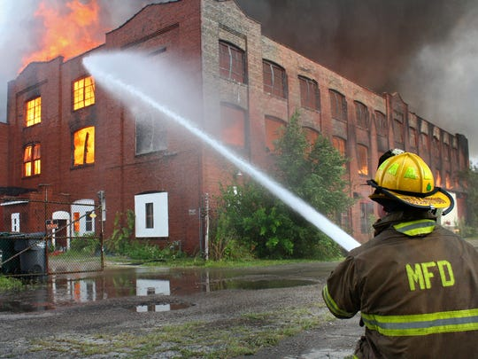 A firefighter from the Muncie Fire Department is shown battling a massive abandoned warehouse fire on Saturday, July 26, 2014. All available firefighters and trucks were called to the blaze, which created enough black smoke it could be seen from anywhere in the city.