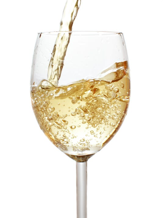 Pouring white wine into a crystal wine glass