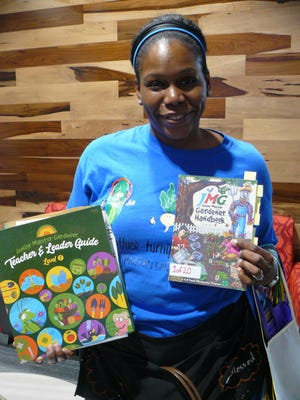 "Melanie Griffin-Hamlin, of Lagos Elementary School in Manor, holds up some of the material for the Junior Master Gardener program. ""I feel like gardening encompasses everything that we want students to know,"" she said. ""We have math, science. We have literacy."""