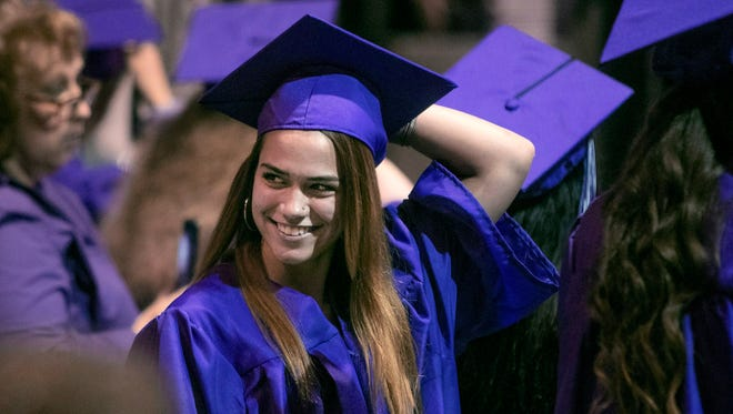 Brooke Winfield catches the eye of a friend during graduation at AIS Diamond High School Tuesday evening. She was nervous before walking on stage, but having friends there helped.