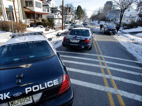 Police converge on a house in Newark, N.J., on Monday, Dec. 16, 2013, in search of suspects in the carjacking at The Mall at Short Hills on Sunday, Dec. 15, 2013. Dustin Friedland, 30, of Hoboken, N.J., was fatally shot during a carjacking at the ups
