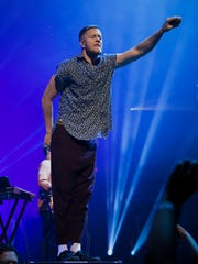 """Imagine Dragons singer Dan Reynolds holds his mic in the air as fans sing """"It's Time"""" during the Evolve Tour launch, Tuesday, September 26, 2017, at Talking Stick Resort Arena in Phoenix."""