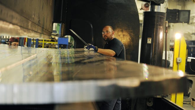 Top: Jason Robinson of Futuramic forms an intertank panel for the Space Launch System.