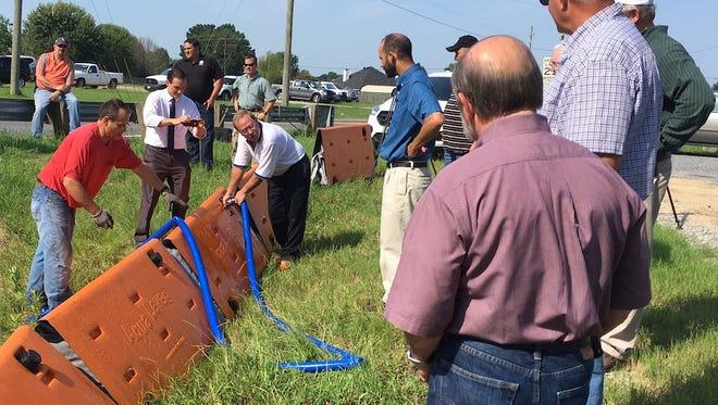 Aqua Levee officials fill units of their flood control system as Bossier Paris officials watch.