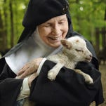 Mother Dolores Hart holds a baby sheep at the Abbey of Regina Laudis in Bethlehem, Conn. The former actress is known for sharing the first on-screen kiss with Elvis Presley.
