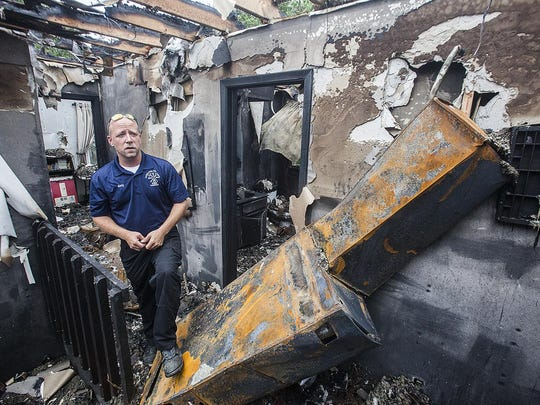 Firefighter Tim Baty walks through the wreckage of a two-story fire that happened early Saturday. The fire fully engulfed the home of Tom and Pam Price who were critically injured during the incident.