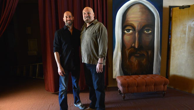 Brian Johnson, left, and Pastor Paul Bergmann pose for a portrait by a painting of Jesus by artist John Adams in the lobby of Ojai Valley Community Church.