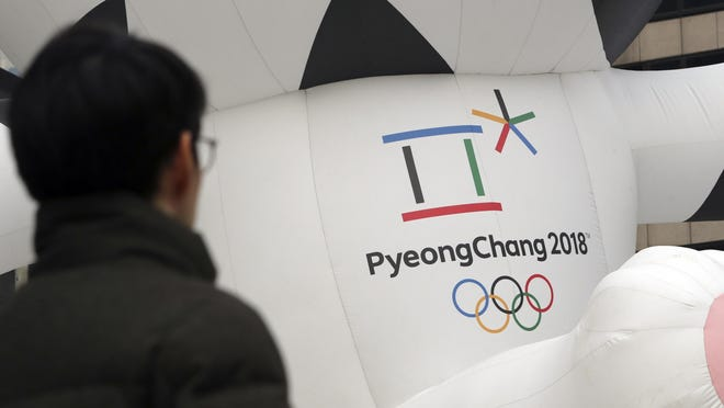 In this Dec. 29, 2017, photo, a man walks by the official emblem of the 2018 Pyeongchang Olympic Winter Games, in downtown Seoul, South Korea. North Korean leader Kim Jong Un said Monday the United States should be aware that his country's nuclear forces are now a reality, not a threat. But he also struck a conciliatory tone in his New Year's address, wishing success for the Winter Olympics set to begin in the South in February and suggesting the North may send a delegation to participate.